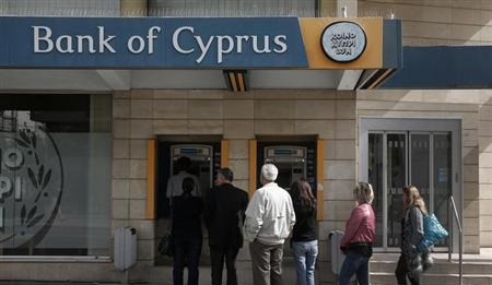People queue up to make a transaction at an ATM outside a branch of Bank of Cyprus in Nicosia