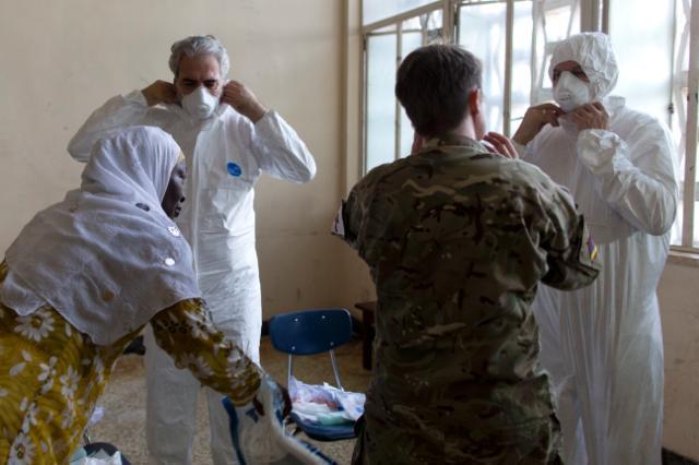 I commissari Andriukaitis e Stylianides indossano le tute protettive prima di visitare uno degli ospedali in cui sono ricoverate le vittime del virus Ebola - ph. Commissione europea