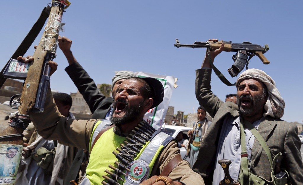 Shi'ite rebels wave their weapons at a checkpoint they erected on a street in Sanaa