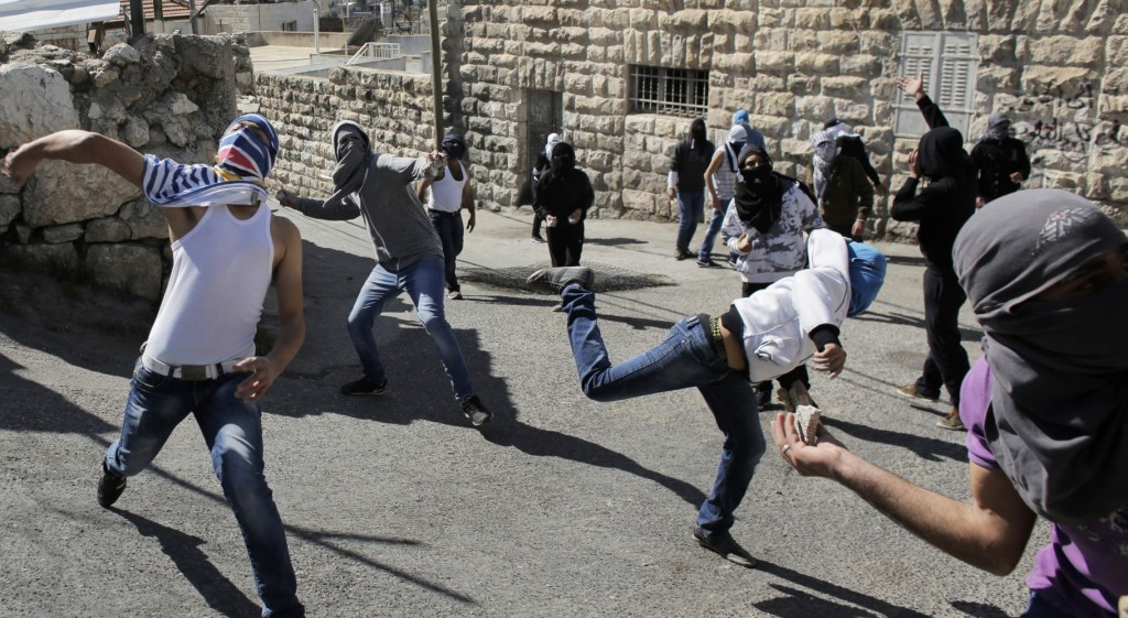 Palestinian protesters throw stones towards Israeli policemen during clashes in the Arab east Jerusalem neighbourhood of Ras al-Amud