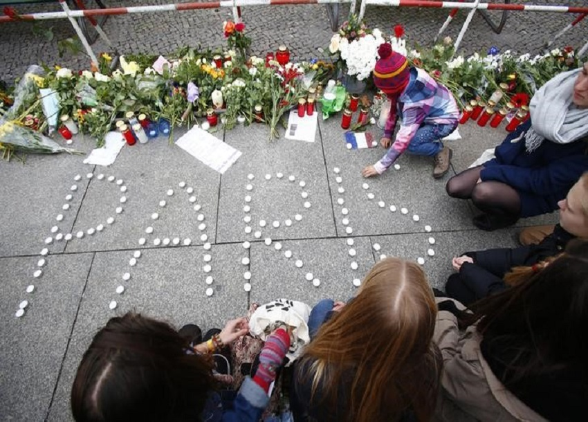 """People place candles to form the word """"Paris"""" outside the French embassy in Berlin"""