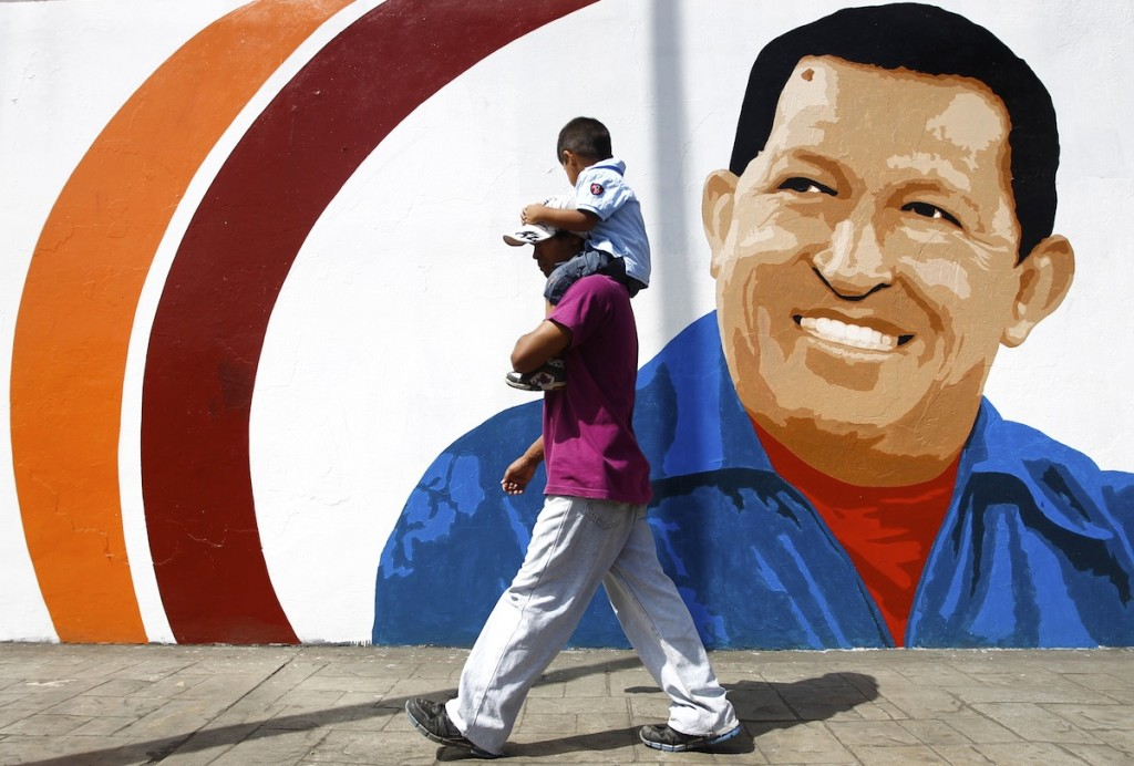 A man carrying a child walks past a mural of Venezuela's President Chavez in Caracas