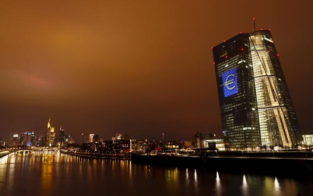 "The head quarter of the European Central Bank (ECB) is illuminated with a giant euro sign at the start of the ""Luminale, light and building"" event in Frankfurt"